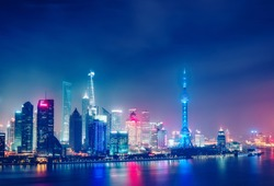 Aerial panoramic view over a big modern city by night. Shangai, China. Nighttime skyline with illuminated skyscrapers.