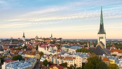 Aerial panoramic view over medieval Old Tallinn cityline with the sunrise colored sky and Moon background