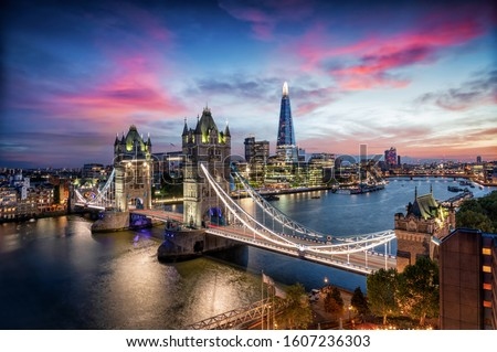 Aerial, panoramic view to the lit Tower Bridge and skyline of London, UK, along the Thames river during dusk time