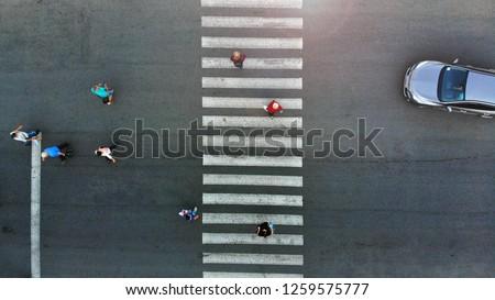 Aerial. Pedestrian crossing crosswalk. People group moving. Car stopped behind a crosswalk.