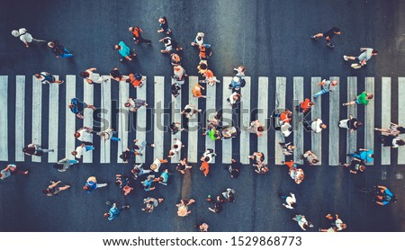 Photo of  Aerial. People crowd motion through the pedestrian crosswalk. Top view from drone. Toned image.