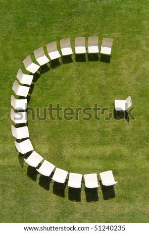 aerial perspective of some chairs arranged in a half circle on a sunny meadow.