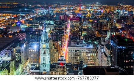 Aerial Philadelphia cityscape by night with the City Hall tower in the foreground and Ben Franklin bridge spanning Delaware river in the back #767783977