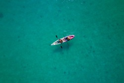Aerial Photo/Bird's eye view - A canoe with two unknown Muslim females in the middle of the sea.