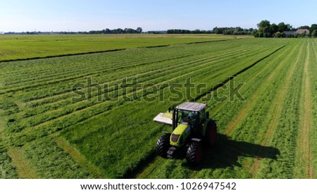 Aerial photo farm scene tractor mowing grass agricultural machinery showing the bright green grass and flat landscape typical Dutch farm meadow pasture landscape