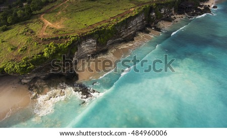 Aerial photo from flying drone of an amazing nature scenery with rock cliff on sandy coastline. Beautiful sea water with waves for surfing in summer season in Bali. Beauty Indian ocean landscape #484960006