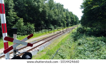 Aerial photo near grade crossing signal forest railway in background railroad also known as the permanent way it enables trains to move by providing dependable surface for their wheels to roll upon