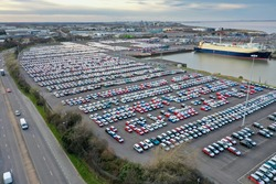 Aerial photo of a car storage yard in the town of Grimsby in the UK, The Vehicle Delivery Service yard is located on the Humber river showing hundreds or brand new cars being waited to board a boat.