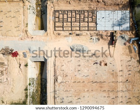 Aerial photo of a crane working on a construction site filling cement into house foundation framing.