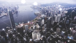 Aerial photo of a Hong Kong cityscape with many skyscapers and development infrastructure. Famous business center megapolis with wireless map of internet comunication and networking connection concept