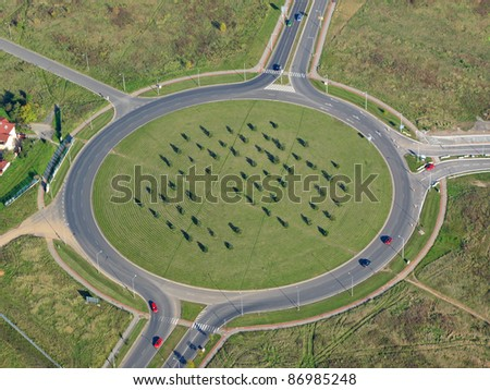 Aerial photo of a roundabout with grass and trees in the middle.