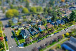 Aerial photo of a small town neighborhood with tilt-shift lens effect applied to give tiny table-top model appearance