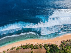 Aerial photo of a wild beach in Bali. A row of sun umbrellas on the beach. Wild beach in Bali with yellow sand and clear turquoise ocean water. Powerful ocean waves roll over the empty beach. Sunny