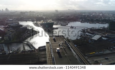 Aerial photo of Amsterdam city center moving over modern office building then showing Nieuwmarkt en Lastage neighbourhood NEMO Science Museum and The National Maritime Museum Stockfoto ©