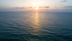 Aerial photo of calm blue ocean waters with orange, white and purple sunset skies and a reflection of the sunset in the water.