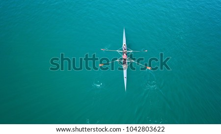 Aerial photo of colourful sport canoes in competition as shot from above in turquoise clear waters