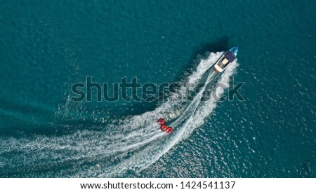 Aerial photo of extreme power boat donut water-sports cruising in high speed in tropical turquoise bay