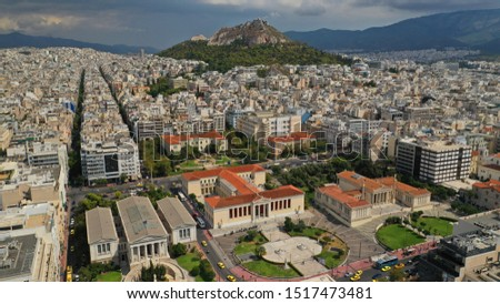 Aerial photo of famous trilogy landmark buildings of Academy of Athens, Panepistimio or University, public Library with iconic Lycabettus hill at the background, Athens, Attica, Greece