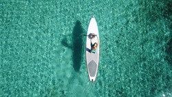 Aerial photo of fit woman paddling on a sup board in caribbean tropical turquoise clear waters