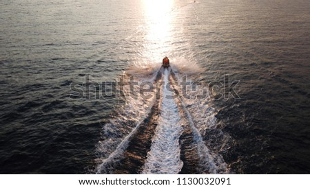 Aerial photo of jet ski cruising in deep blue mediterranean sea at sunset