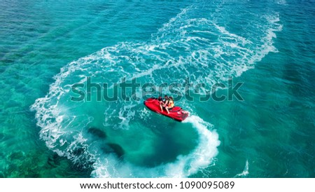 Aerial photo of jet ski with couple cruising in low speed in Caribbean tropical crystal clear waters