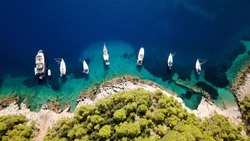 Aerial photo of luxury sail boat docked in tropical caribbean rocky turquoise color seascape