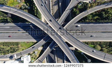 Aerial photo of multilevel elevated highway junction highway passing through modern city in multiple directions #1269907375