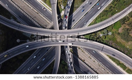 Aerial photo of multilevel elevated highway junction highway passing through modern city in multiple directions #1388165885