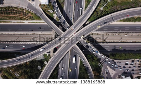 Aerial photo of multilevel elevated highway junction highway passing through modern city in multiple directions #1388165888
