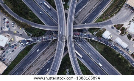 Aerial photo of multilevel elevated highway junction highway passing through modern city in multiple directions #1388165894