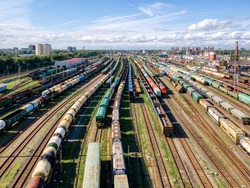 Aerial photo of railway terminal. Freight wagons with goods on railroad station. Cargo transportation. Import and export logistics. Industrial landscape. Top view from drone. Heavy industry.