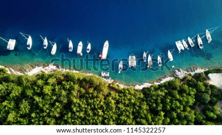Aerial photo of sail boats and yachts docked in traditional fishing village of Fiskardo, Kefalonia island, Ionian, Greece