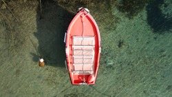 Aerial photo of small red fishing boat docked in port