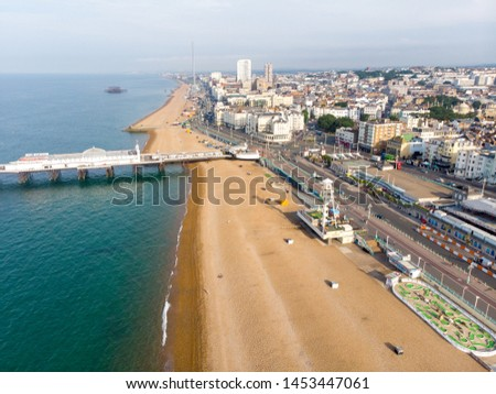 Aerial photo of the Brighton beach and coastal area of the City of Brighton and Hove, with the Brighton Pier in the background taken on a bright sunny day.