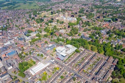 Aerial photo of the Lincoln Cathedral, Lincoln Minster in the city centre of Lincoln on a bright sunny summers day showing the historic Cathedral Church in the city centre and rows of houses