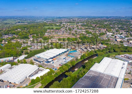 Aerial photo of the town centre of Dewsbury in West Yorkshire in the UK showing factories and buildings along side the the river calder on a blue sky day with clouds in the sky