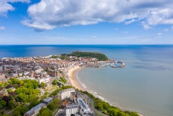Aerial photo of the town centre of Scarborough in East Yorkshire in the UK showing the coastal beach and harbour with boats and the Scarborough Castle on a bright sunny summers day
