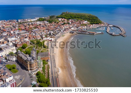 Photo of  Aerial photo of the town centre of Scarborough in East Yorkshire in the UK showing the coastal beach and harbour with boats and the Scarborough Castle on a bright sunny summers day