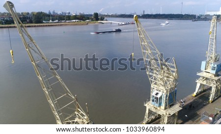 Aerial photo of three harbor cranes and in background barge over Scheldt river harbor landscape located in Antwerp Belgium industrial background Antwerp is important harbor area for Europe