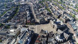 Aerial photo taken from helicopter of Amsterdam city center Dam Square also showing national monument the Royal Palace and the New Church popular tourist attraction in the Netherlands
