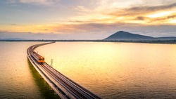 Aerial Photo The train is running on the bridge Over lake Pa Sak Dam Lopburi Thailand beautiful sunlight Golden hour