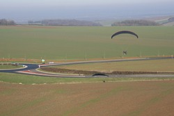 Aerial photograph of a paramotor (motorized paraglider) flying over a roundabout in soindres fields, Yvelines department (78200), Ile-de-France region, France - January 03, 2010