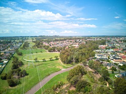 Aerial photograph of Blue Hills playing field sports oval cricket pitch with large overland power lines in foreground, green trees and houses on sunny autumn day