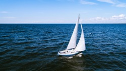 Aerial photography of yacht with white sails in dark blue open space. The good wind fills sails on a sunny summer day.