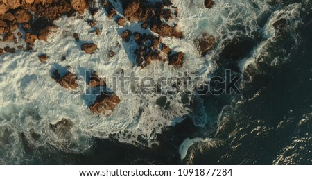 Aerial photography. Strong storm, big waves. The waves break against the rocky shore. View from above.