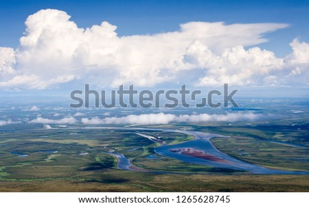 Aerial photography. Top view of the Anadyr River and beautiful clouds. The endless expanses of tundra in the Arctic. Many lakes on the plain. Summer. Chukotka, Siberia, Far East of Russia.