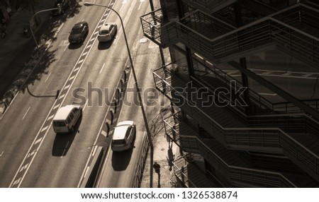 Aerial pic of the road  with few car and of a building with mirror windows, in a day with very deep shadows. Street of Madrid, Spain. Perfect background for the concept a hot day in an urban city