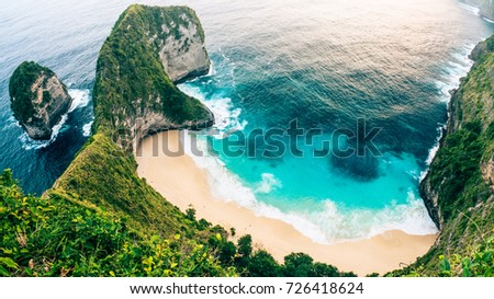 Aerial picture of a cliff with crystal blue water and gold beach in Indonesia. Bali landscape from top view from a mountain peak. Travel paradise destination for a couple in searching for adventure.