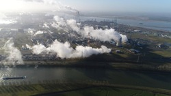 Aerial picture of nuclear power plant and cargo vessel barge moving over canal a thermal power station in which the heat source is a nuclear reactor this plant is located in a heavy industrial zone