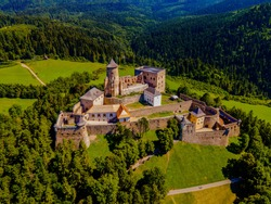 Aerial picture of Stara Lubovna Castle, Slovakia, famous medieval castle on a small hill surrounded by a green forest and fields on summer sunny day